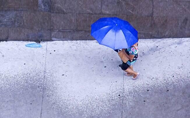 Pedestre se protege da chuva na Avenida Rangel Pestana em São Paulo (SP), nesta sexta-feira (01)