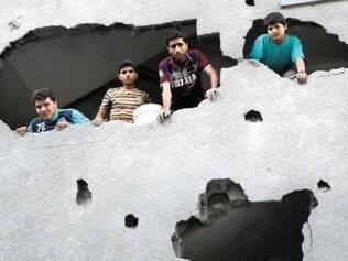 Destruição. Palestinos verificam os danos causados por foguete israelense a prédio na Faixa de Gaza