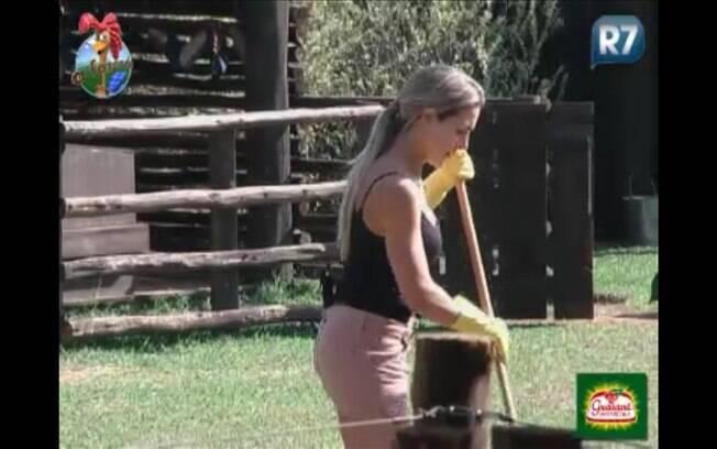 Fazendeira varre pátio da fazenda