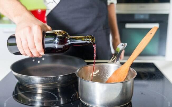 Cozinheiro colocando vinho tinto em uma panela