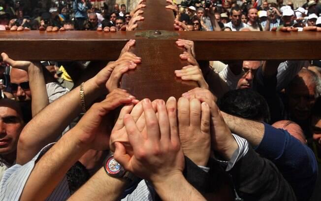 Fiéis percorrem a Via Dolorosa carregando uma cruz