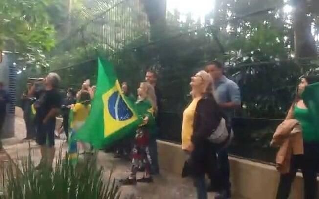 pessoas com bandeira diante de prédio