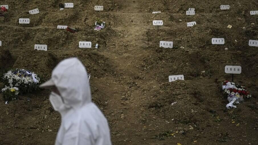 Coveiro passando por vítimas da codi-19 enterradas no cemitério