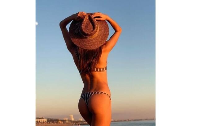 Alessandra Ambrósio de biquíni em meio a praia e pôr do sol