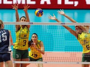 United States' Kimberly Hill, left, spikes the ball against Brazil's Danielle Lins, center, and teammate Thaisa Menezes during a semifinal volleyball match between United States and Brazil, at the women's Volleyball World Championships in Milan, Italy, Saturday, Oct. 11, 2014. (AP Photo/Felice Calabro')