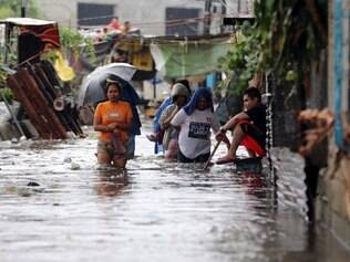 TUFAO NAS FILIPINAS Residents wade along a flooded road as Typhoon Rammasun nears suburban Quezon city, Philippines on Wednesday, July 16, 2014. Typhoon Rammasun knocked out power in many areas but it spared the Philippine capital, Manila, and densely-populated northern provinces from being directly battered Wednesday when its fierce wind shifted slightly away, officials said.  (AP Photo/Aaron Favila)