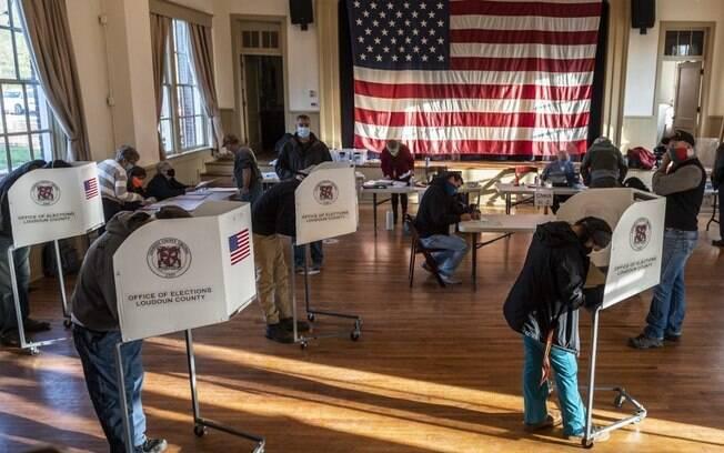 Americanos votando presencialmente nas cédulas que decidirão o próximo presidente do país