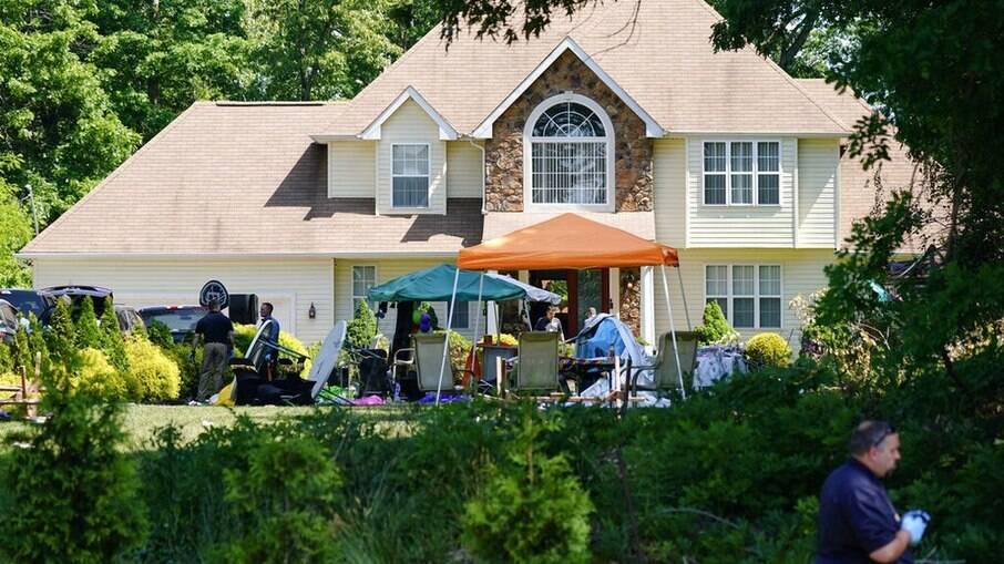Casa em Nova Jersey onde aconteceu a festa e o tiroteio; policiais investigam o local na manhã de domingo (23)