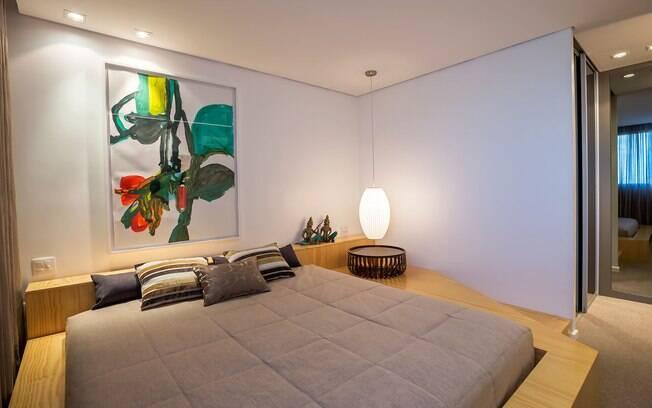 Neste quarto a opção foi por levantar a cama com tablado de madeira, que se desdobra e conforma uma cabeceira baixa