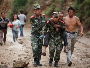 In this photo released by China's Xinhua News Agency, rescuers transport injured people after an earthquake in Zhaotong City in the densely populated Ludian county in southwest China's Yunnan Province, Sunday Aug. 3, 2014.  The strong earthquake in southern China's Yunnan province toppled thousands of homes on Sunday, killing at least 175 people and injuring more than 1,400, according to China's official Xinhua News Agency. (AP Photo / Xinhua, Zhang Guangyu) NO SALES
