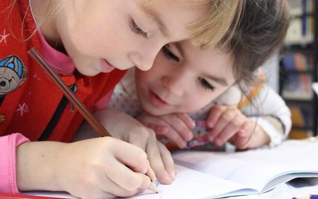 duas meninas olhando para um livro enquanto uma escreve