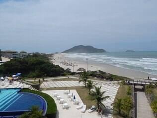 Complexo de hospedagem com área de piscina e vista geral da praia