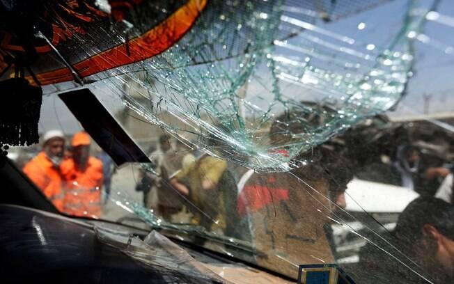 Afegãos são vistos através da janela quebrada de um carro danificado no local onde ocorreu ataque suicida em Cabul, Afeganistão