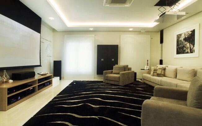 Projetor, telão e caixas de som aparecem apenas quando necessário no home theater projetado por Cristiane Schiavoni