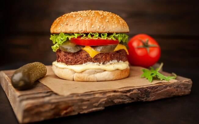 Imagem ilustrando um hambúrguer com seus ingredientes ao lado.