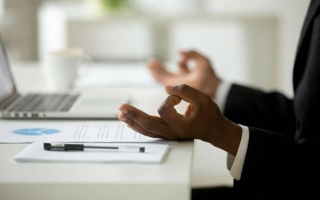 Homem meditando na mesa de trabalho