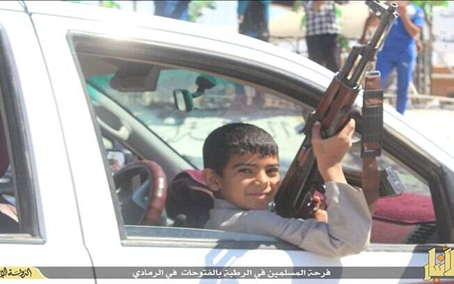 Criança com arma de fogo em mãos participa de parada comemorativa do EI em cidade do Iraque