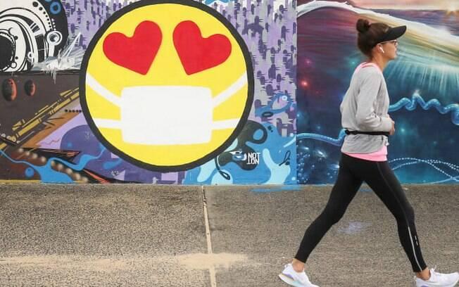 Uma pedestre passa por um mural representando um emoji vestindo uma máscara protetora ao longo do passeio na praia de Bondi, em Sydney