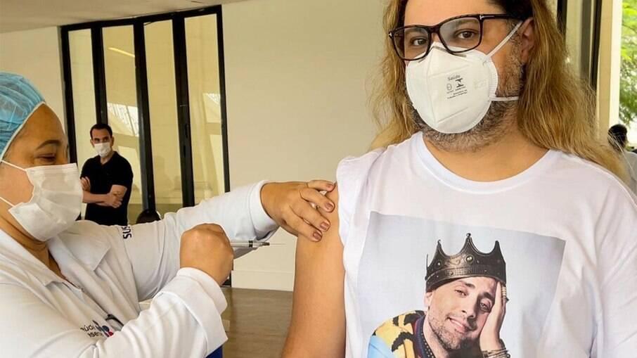 Marcos Majella toma vacina usando camiseta com rosto de Paulo Gustavo