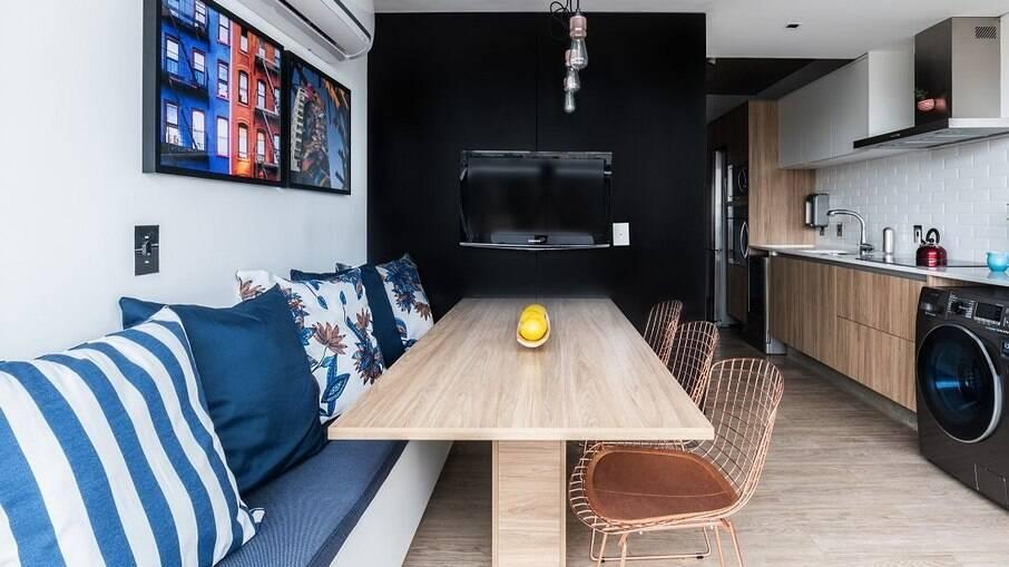 Colocado entre a cozinha e varanda, recebeu um banco baú branco com detalhes em azul e três cadeiras Bertoia em cobre