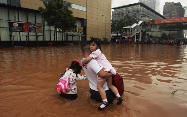Pai atravessa com filhas rua inundada em distrito comercial de Jacarta (17/01/2013). Foto: Reuters