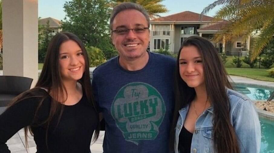 Gêmeas de Gugu posam ao lado do pai