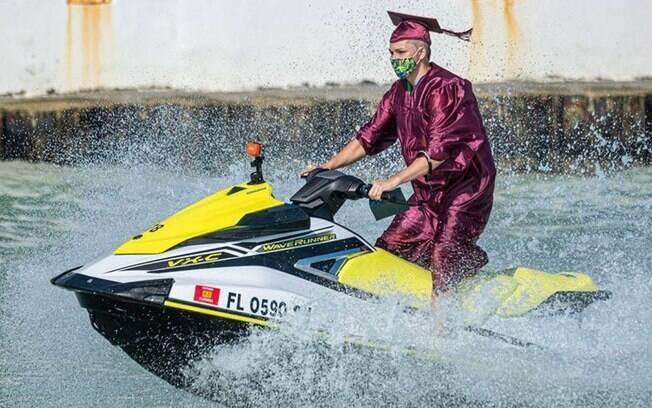Um graduado da Somerset Island Prep, uma escola em Key West, vai à água para receber o diploma
