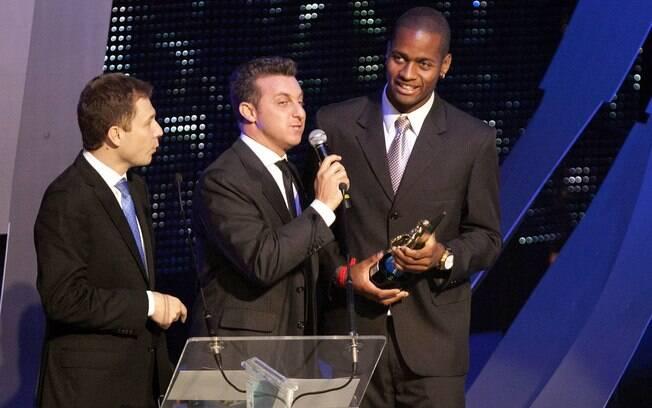 Dedé recebe de Tiago Leifert e Luciano Huck o  prêmio de melhor zagueiro pela direita