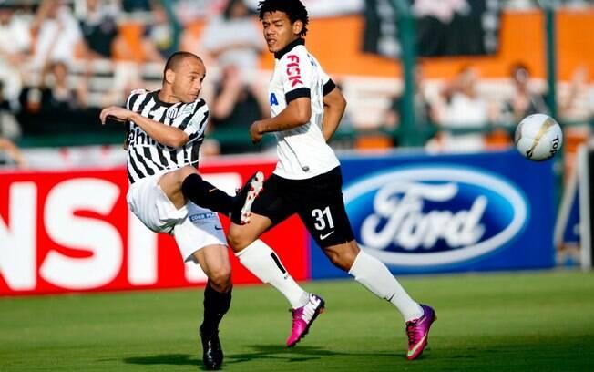 O lateral santista Léo afasta a bola, sob o  olhar do atacante corintiano Romarinho