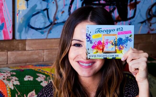 Érika faz graça com os panfletos do TOCAYO, primeiro evento da sua produtora AUCH