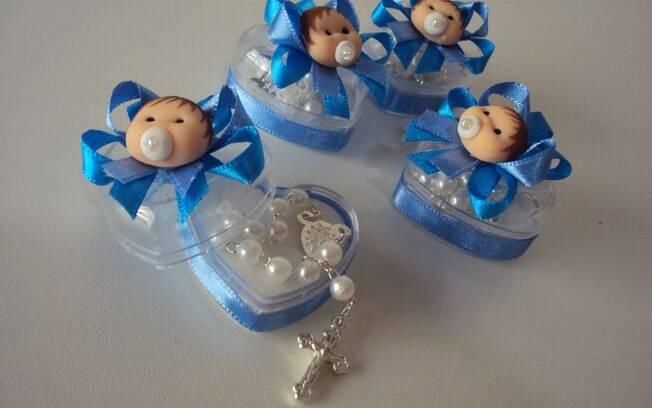 Enfeitado com um bebê de biscuit, o pequeno porta-joias com um mini terço