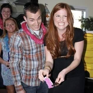 Ashley Brickner e o marido mostram o bolo rosa: ela estava grávida de uma menina