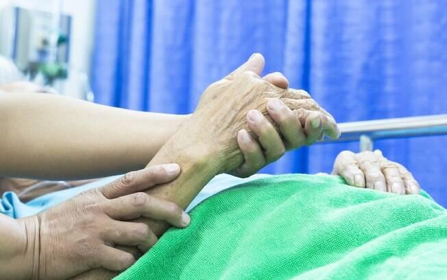 alguém segurando mão de idosa no hospital
