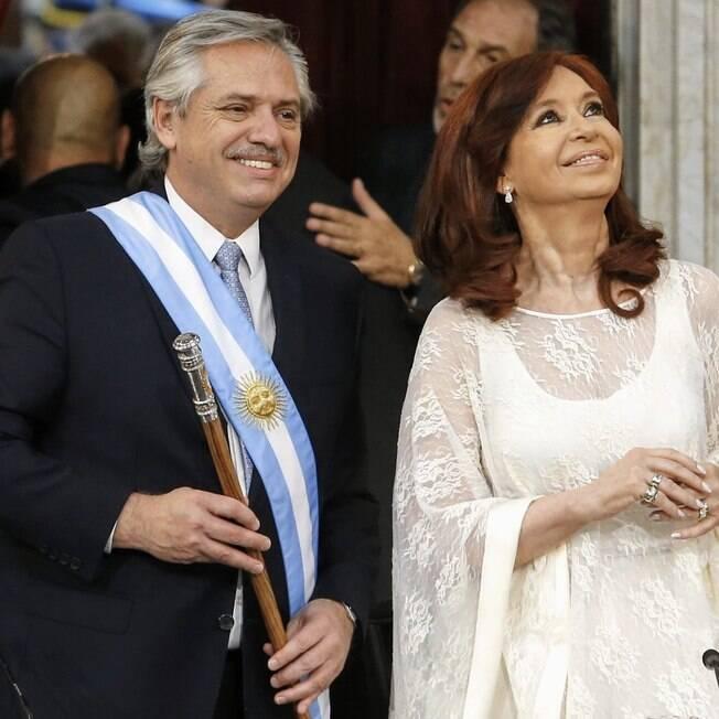 Alberto Fernández, com faixa presidencial, e Cristina Kirchner olhando para cima