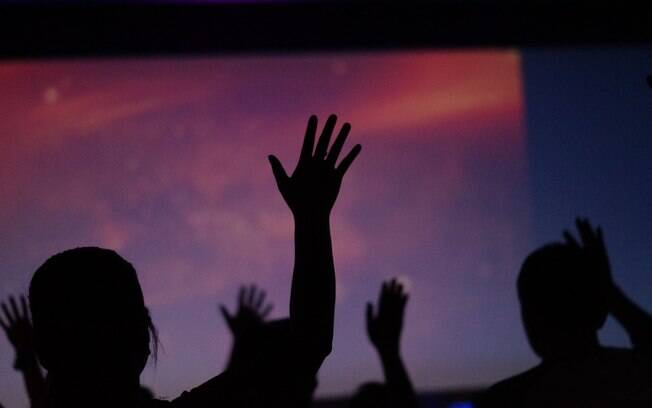pessoas contra a luz e com mãos para cima
