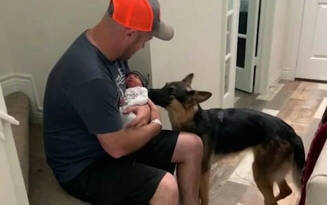 Chris, o novo papai, segurando Jaxson no colo, sentado na escada da sua casa