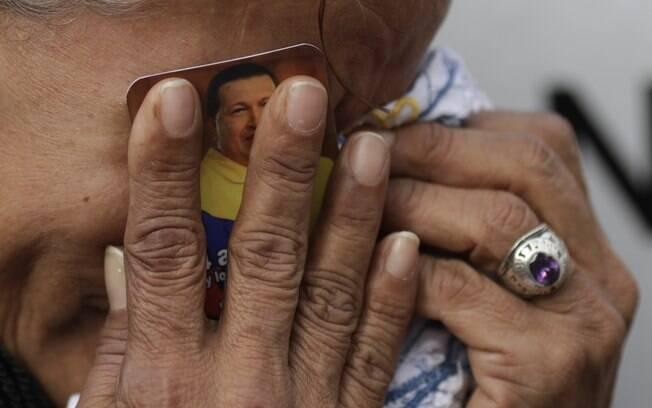 Venezuela chora segurando foto do presidente da Venezuela, Hugo Chávez, contra o rosto do lado de fora de hospital militar em Caracas (06/03)