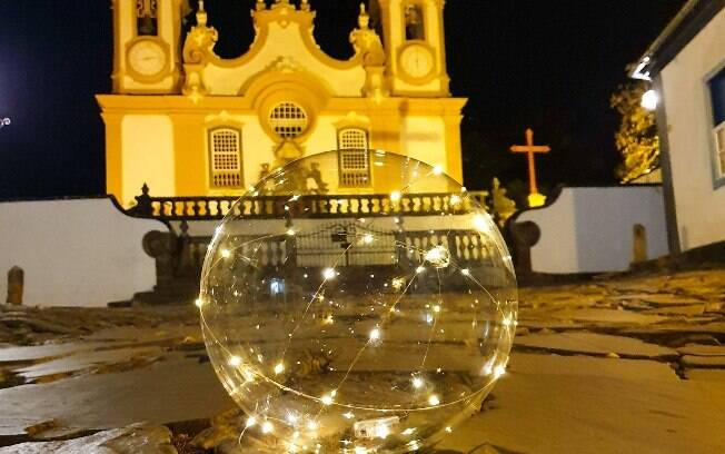 Bola de Natal transparente no chão em frente à Igreja de Santo Antônio em Tiradentes