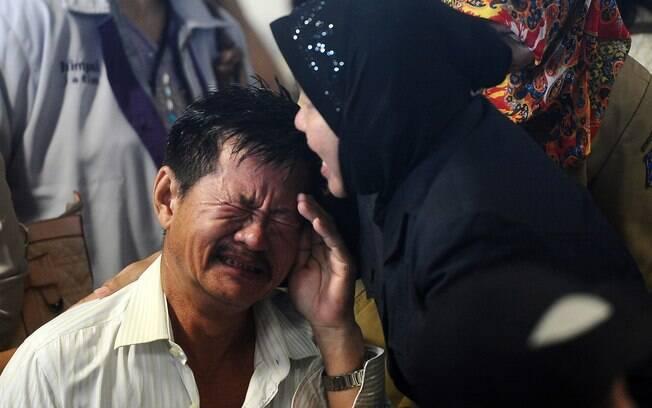 Parentes de passageiros do voo AirAsia QZ8501 reagem à notícia de que detritos e corpos foram encontrados no Mar de Java nesta terça-feira 30 de dezembro. Foto: Robertus Pudyanto/Getty Images