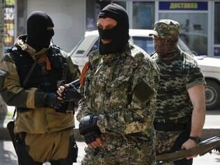 Pro-Russian masked gunmen patrols a street  in the center of Slovyansk, eastern Ukraine, Wednesday, April 23, 2014. Pro-Russian gunmen in eastern Ukraine admitted on Wednesday that they are holding an American journalist, saying he was suspected of unspecified