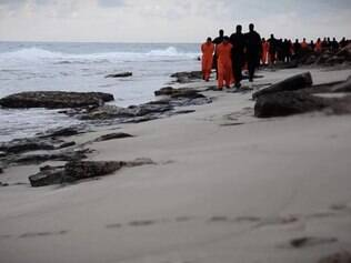 An image grab taken from a video released by the jihadist media arm Al-Hayat Media Centre on February 15, 2015 purportedly shows black-clad Islamic State (IS) group fighters leading handcuffed hostages, said to be Egyptian Coptic Christians, wearing orange jumpsuits before their alleged decapitation on a seashore in the Libyan capital of Tripoli. AFP PHOTO / HO / AL-HAYAT MEDIA CENTRE === RESTRICTED TO EDITORIAL USE - MANDATORY CREDIT