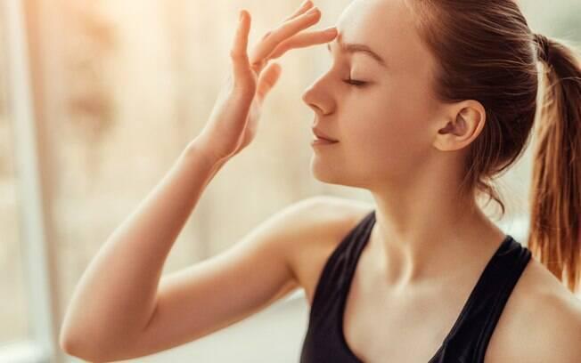 Mulher massageando o espaço entre as sobrancelhas