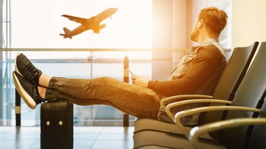 Homem com celular na mão e pés apoiados na mala, observando um avião decolar
