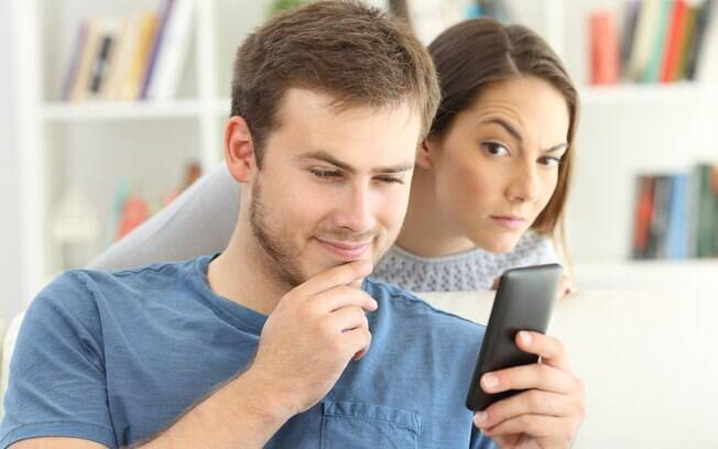 homem mexe no celular; ao fundo, mulher olha desconfiada