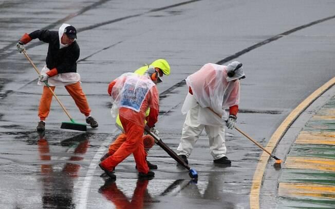 Funcionários tentam remover excesso de água  na pista do circuito de Melboune, na Austrália,  durante treino classificatório