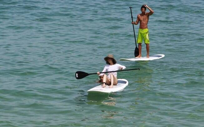 Fernanda Torres se protege do sol enquanto tem aulas de surfe