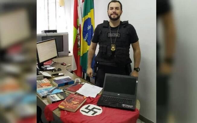 homem policial posando com artigos de nazismo
