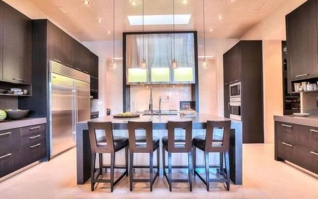 A cozinha da mansão reúne um contraste entre o clássico e o contemporâneo ao apostar em armários grandes e escuros