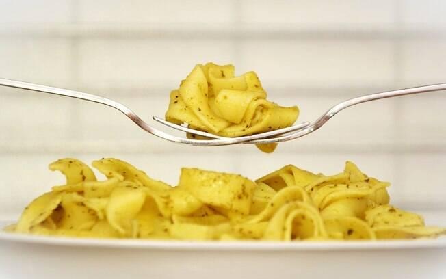 Macarrão caseiro em um prato, com uma pessoa pegando uma porção com um garfo.