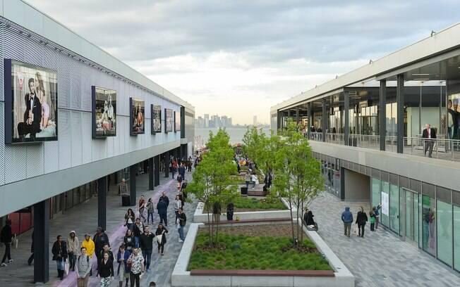 Visitantes caminhando pelo boulevard do Empire Outlets